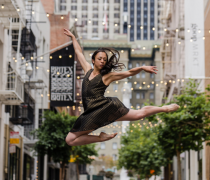 ballet dancer in mid air, in the  middle of a city street