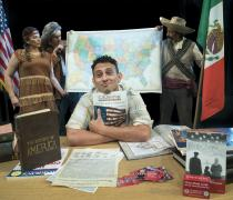actor sitting at desk with books all around him. Behind him are a revolutionary soldier holding mexican flag, an american indian holding a map.
